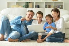 Famille à la maison avec l'ordinateur portatif Photos stock