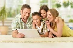 Famille à la maison avec l'ordinateur portatif Photos libres de droits