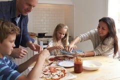 Famille à la maison dans la cuisine faisant des pizzas ensemble photos libres de droits