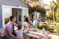 Famille à la maison mangeant le repas extérieur dans le jardin ensemble images stock
