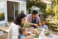 Famille à la maison mangeant le repas extérieur dans le jardin ensemble image stock