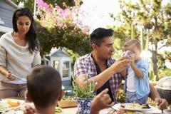 Famille à la maison mangeant le repas extérieur dans le jardin ensemble photos stock