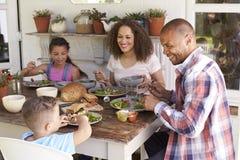 Famille à la maison mangeant le repas extérieur ensemble Photographie stock libre de droits