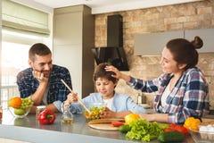 Famille à la maison se penchant sur la table dans des parents de cuisine ensemble regardant le sourire de mélange de salade de fi images libres de droits