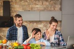 Famille à la maison se tenant dans la cuisine ayant ensemble le faire appel visuel à l'ordinateur portable avec le sourire de gra images stock