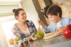 Famille à la maison se tenant en plan rapproché gai de aide de mélange de maman de salade de fils de cuisine ensemble photographie stock