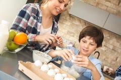 Famille à la maison se tenant près de la table en mère de cuisine ensemble et plan rapproché gai beaking d'oeufs de fils photographie stock libre de droits