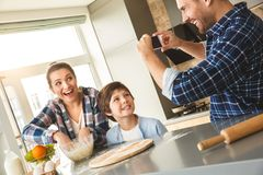 Famille à la maison se tenant à la table dans le père de cuisine ensemble prenant des photos de la mère et le fils faisant cuire  images stock