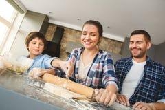 Famille à la maison se tenant à la table en père de cuisine ensemble et pâte de roulement de aide de mère de fils ajoutant la far photo stock