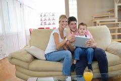Famille à la maison utilisant la tablette Photographie stock libre de droits