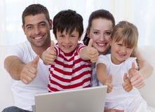 Famille à la maison utilisant un ordinateur portatif avec des pouces vers le haut Photographie stock libre de droits