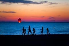 Famille à la plage allumant une lanterne chinoise de bougie Photographie stock