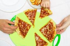 Famille à une table ronde mangeant de la pizza Images libres de droits