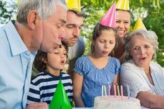 Famille étendu dans des chapeaux de partie soufflant le gâteau d'anniversaire Images libres de droits