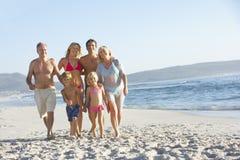 Famille étendu marchant le long de Sandy Beach By Sea Images libres de droits