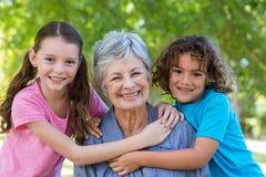 Famille étendu souriant et embrassant en parc Photo libre de droits