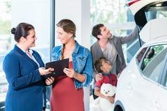 Famille achetant la nouvelle voiture dans la salle d'exposition de concessionnaire automobile photo stock