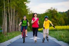 Famille active - mère et enfants courant, faire du vélo, faisant du roller Photographie stock libre de droits