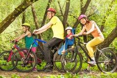 Famille active sur des vélos montant dans la forêt ensoleillée Photographie stock