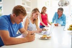 Famille adolescente prenant le petit déjeuner dans la cuisine avec l'ordinateur portable Photo stock