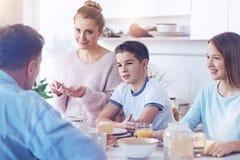 Famille adorable écoutant le père parlant pendant le repas de famille Image stock