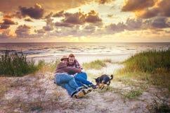 Famille affectueuse à la mer de coucher du soleil Image stock