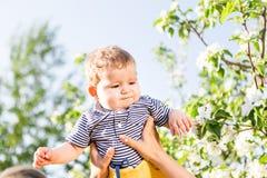 Famille affectueuse heureuse avec le fils de bébé dans le jardin de floraison de ressort Enfantez la chéri de fixation Passant le Photos libres de droits