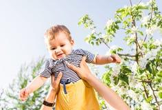 Famille affectueuse heureuse avec le fils de bébé dans le jardin de floraison de ressort Enfantez la chéri de fixation Passant le Photos stock