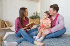 Famille affectueuse heureuse Mère assez jeune lisant un livre à sa fille Image libre de droits