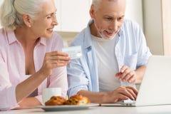 Famille affectueuse mûre heureuse de couples utilisant l'ordinateur portable tenant la carte de crédit Image libre de droits