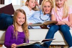 Famille affichant un livre ensemble Photographie stock libre de droits