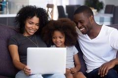 Famille africaine heureuse avec l'enfant ayant l'amusement à l'aide de l'ordinateur portable ensemble photographie stock libre de droits