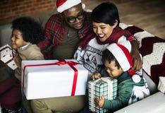 Famille africaine heureuse célébrant avec des cadeaux de Noël image stock