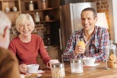 Famille agréable ayant une vie sociale tout en prenant le petit déjeuner Photographie stock