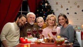Famille amicale étreignant et regardant dans la caméra, traditions de dîner de Noël photo libre de droits