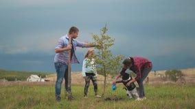 Famille amicale, enfants plantant l'arbre avec le parent dans le jardin banque de vidéos