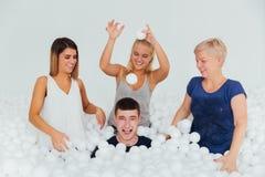 Famille amicale heureuse entourée par les boules en plastique blanches dans la piscine sèche Photo libre de droits