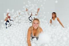 Famille amicale heureuse entourée par les boules en plastique blanches dans la piscine sèche Images stock