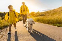 Famille amicale voyageant en nature avec l'animal familier Photo stock