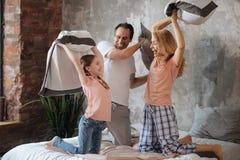 Famille amusée appréciant le combat d'oreiller à la maison image libre de droits