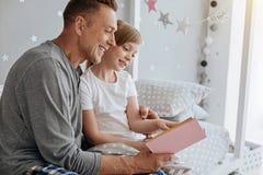 Famille animée avec du charme lisant une histoire gentille ensemble Photo libre de droits