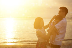 Famille appréciant des vacances de vacances sur le bord de la mer dans le coucher du soleil Photos libres de droits