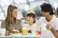Famille appréciant le casse-croûte au café