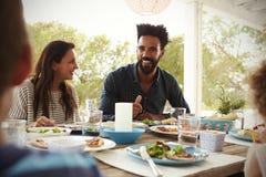 Famille appréciant le repas extérieur sur la terrasse ensemble Image libre de droits
