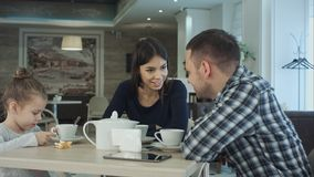 Famille appréciant le thé en café ensemble Père et mère parlant regardant leur fille Images libres de droits