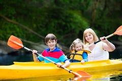 Famille appréciant le tour de kayak sur une rivière image stock