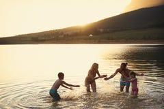 Famille appréciant même le bain dans le lac countryside images stock