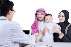Famille Arabe avec le pédiatre dans le studio Photographie stock libre de droits