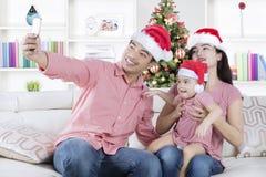 Famille asiatique avec le chapeau et le smartphone de Santa Images stock
