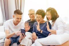 Famille asiatique avec les enfants adultes et les parents supérieurs faisant un appel visuel et ondulant au visiteur à la maison Images libres de droits